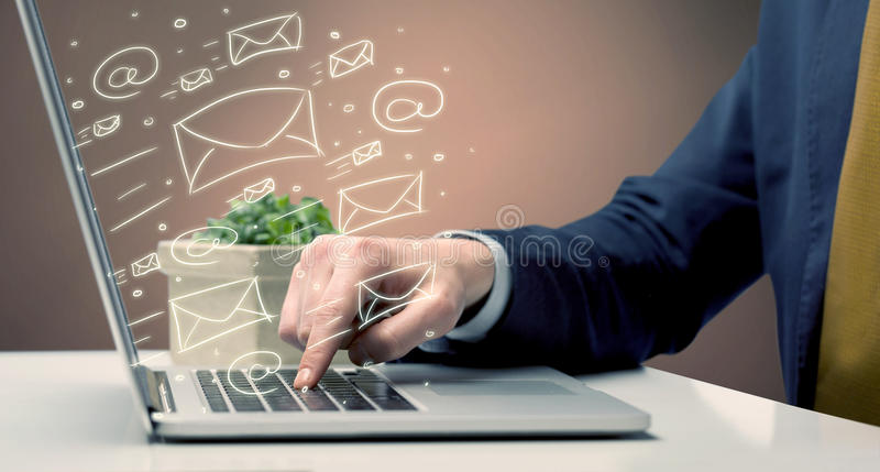 Sending client news letters on laptop. An office worker sending emails and communication with clients with the help of a portable laptop on desk concept stock photos