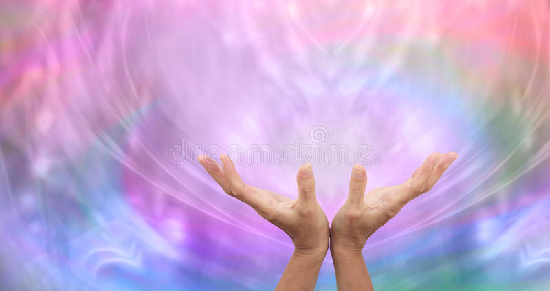 Sending Distant Healing. Healer's open hands sending distant healing with misty multicolored energy formation in background royalty free stock image