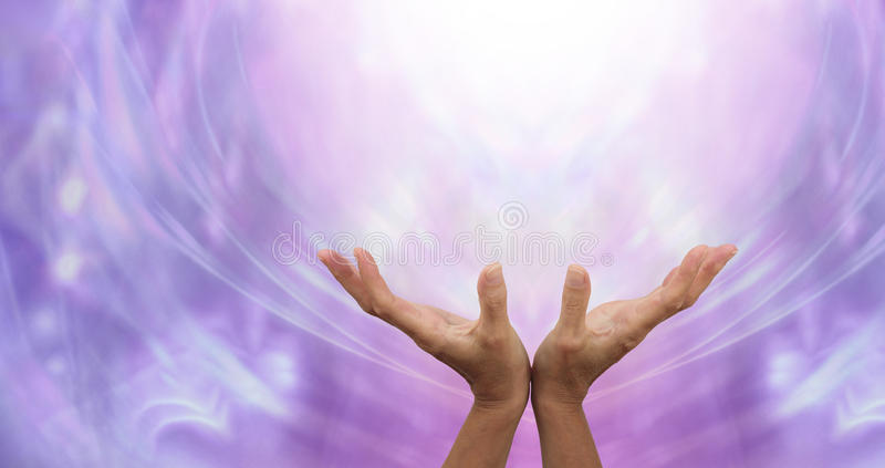 Sending Distant Healing into the Light. Female hands outstretched sending healing into the light above and an ethereal purple energy formation background stock image