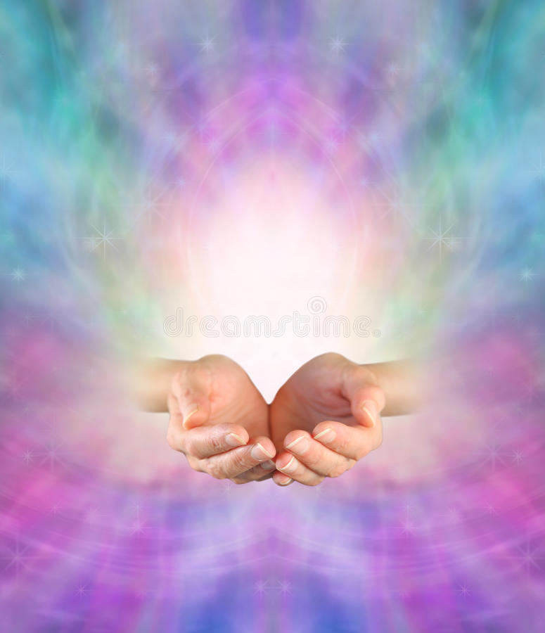 Sending Divine Healing Energy. Female with cupped hands on an ethereal pink and blue energy formation background and a burst of white light rising up stock photos