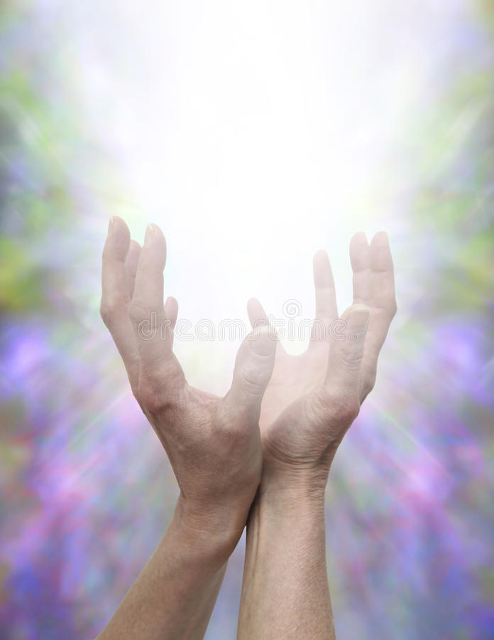 Sending Healing Energy. Female healing hands cupped and reaching upwards with white light between palms with a beautiful delicate angelic energy formation stock images