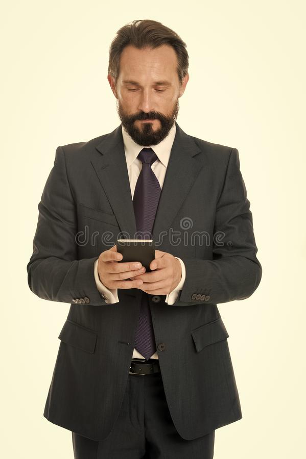 Sending important message. Businessman formal suit holds smartphone. Man bearded businessman concentrated on texting. With colleague. Checking email or sending stock images