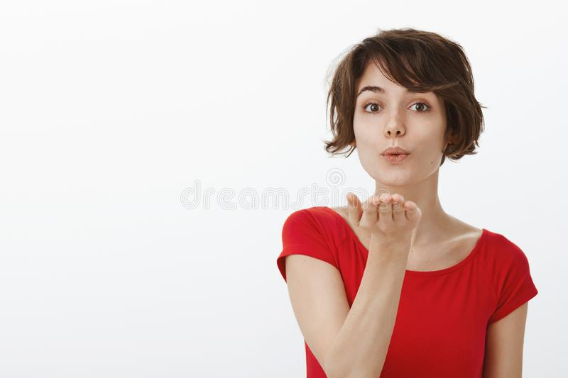 Sending only positivity and love. Tender cute european girl short stylish haircut folding lips silly gently blowing air royalty free stock photos