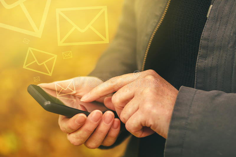 Sending SMS messages on mobile phone in autumn stock photography
