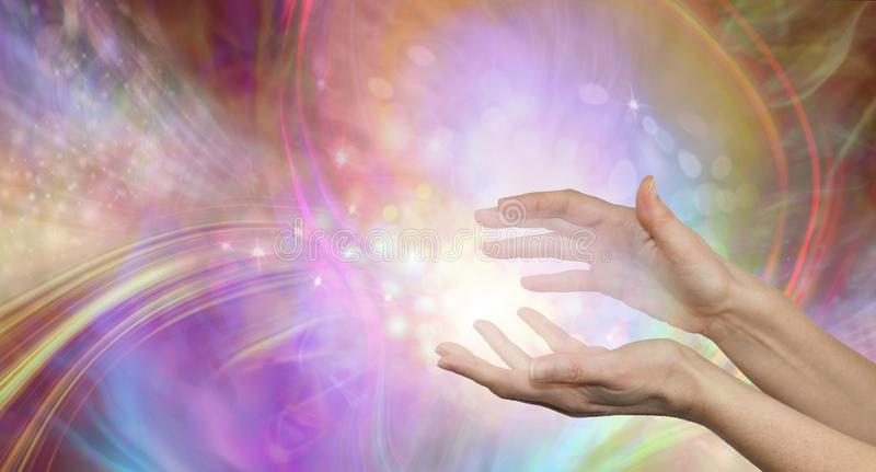 Sending you beautiful healing energy vibes. Female cupped hands with white energy formation flowing outwards, sparkles and colours moving in all directions with stock image