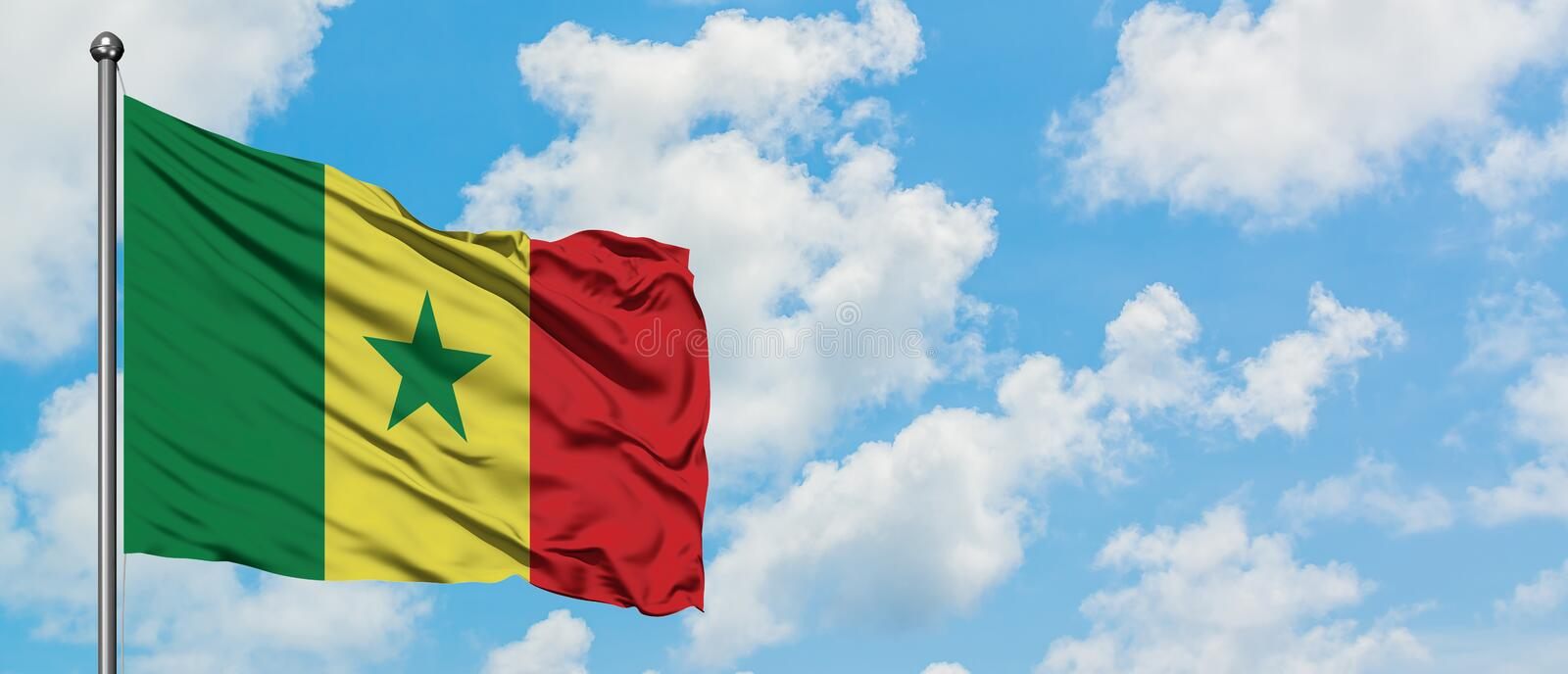 Senegal flag waving in the wind against white cloudy blue sky. Diplomacy concept, international relations.  stock image