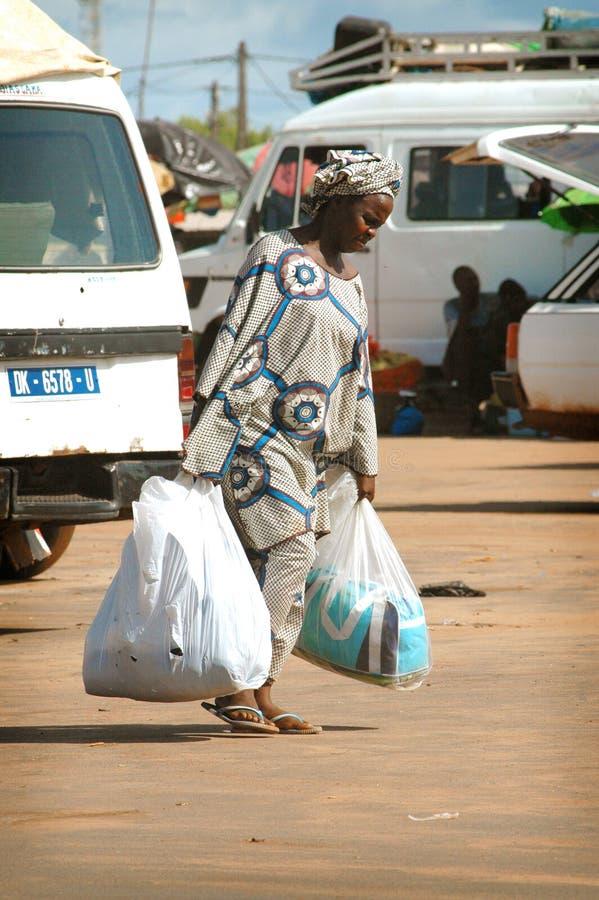 SENEGAL - 12. JUNI: Eine Frau, die in die Straße mit großen Taschen O geht lizenzfreie stockfotografie
