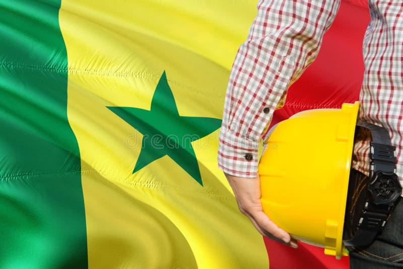 Senegalski inżynier trzyma żółtego zbawczego hełm z machać Senegal chorągwianego tło Budowy i budynku poj?cie obrazy stock