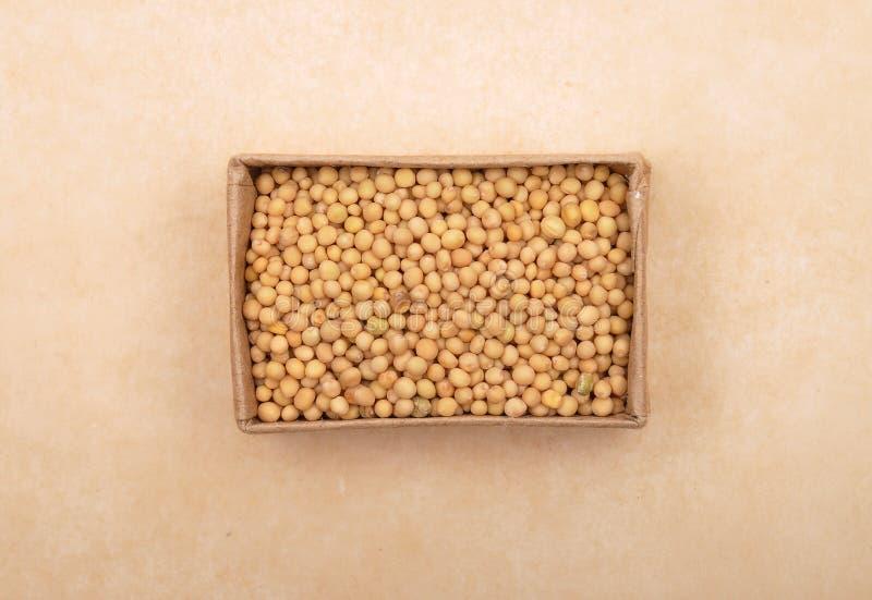 Senfkorn im Karton auf braunem Hintergrund stockfotografie