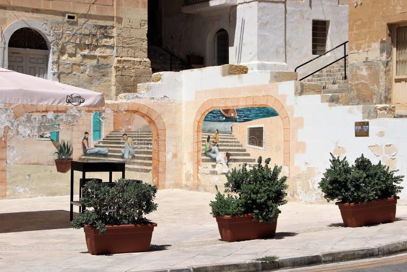 Senglea, Malta, em julho de 2015 Um quadrado pequeno na terraplenagem com as paredes pintadas por um artista local imagens de stock royalty free