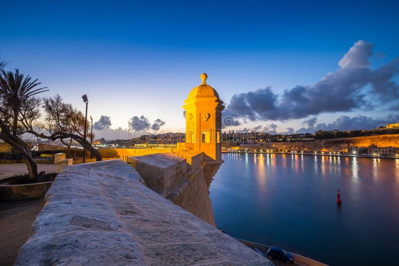 Senglea, Malta - Watch tower at Fort Saint Michael, Gardjola Gardens. And the walls of Valletta at blue hour with beautiful sky and clouds royalty free stock photography