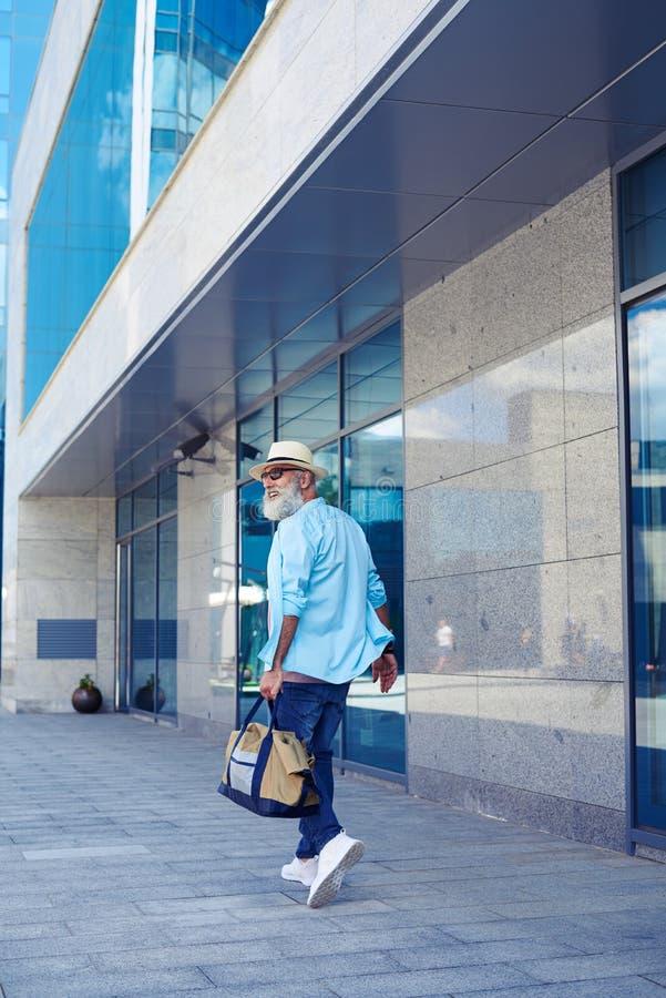 Senhor considerável que anda abaixo da rua ao levar a bolsa foto de stock royalty free