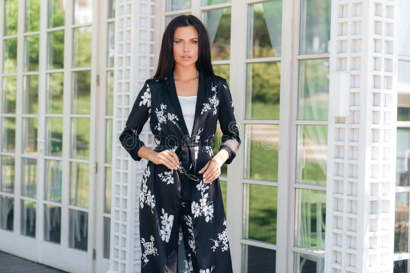 A senhora à moda bonita do negócio tem uma aparência europeia, morena Encontra seus colegas no patamar, guarda o seu imagens de stock