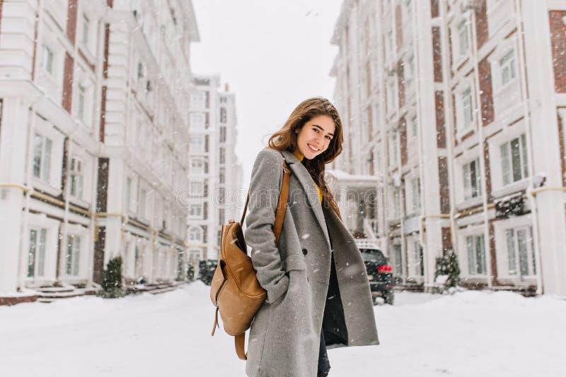 Senhora à moda com trouxa marrom que anda em torno da cidade sob a queda de neve Foto exterior da menina bonita com sorriso de en imagens de stock