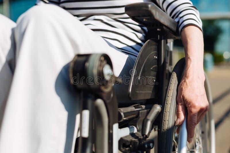 Senhora à moda envelhecida brilhante que conduz a cadeira de rodas fotografia de stock royalty free