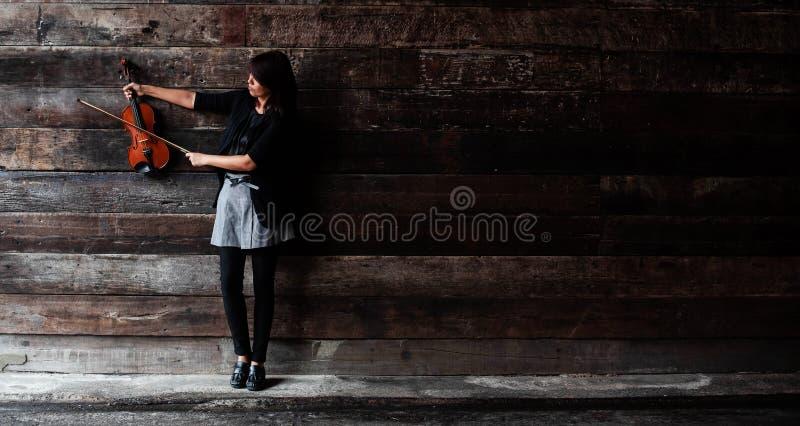 A senhora é violino da posse e braço direito estendido, aumento da formiga da curva da posse da mão esquerda para tocar na corda foto de stock
