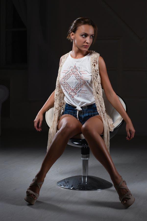 Senhora adorável que levanta o assento em uma cadeira fotografia de stock royalty free
