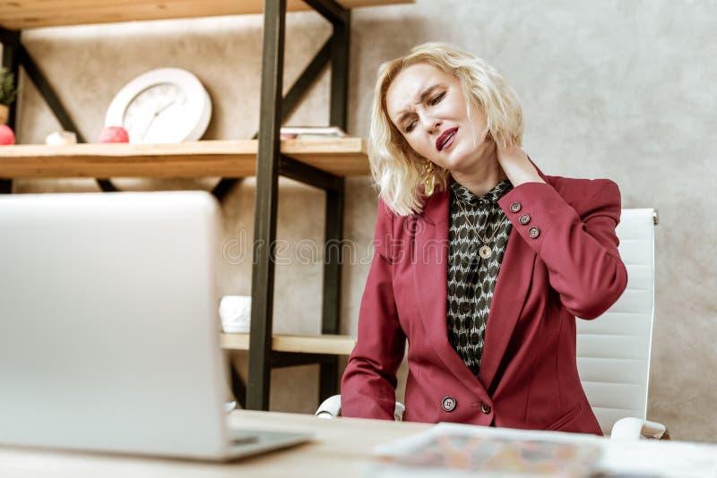 Senhora adulta de sofrimento no revestimento vermelho que torce sua cara durante sentimentos dolorosos fotografia de stock
