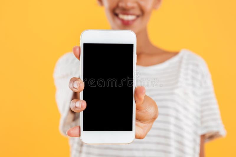 Senhora africana feliz que mostra o smartphone com a tela vazia isolada imagens de stock