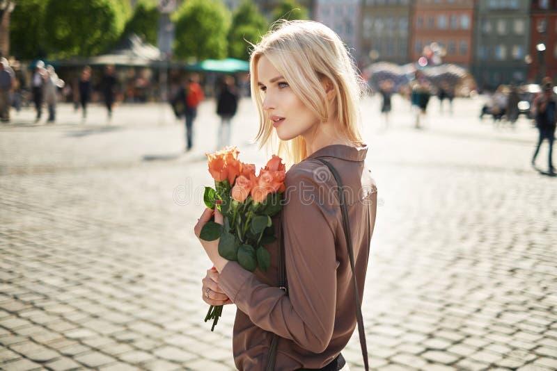 Senhora alegre que guarda um ramalhete de rosas frescas fotos de stock royalty free