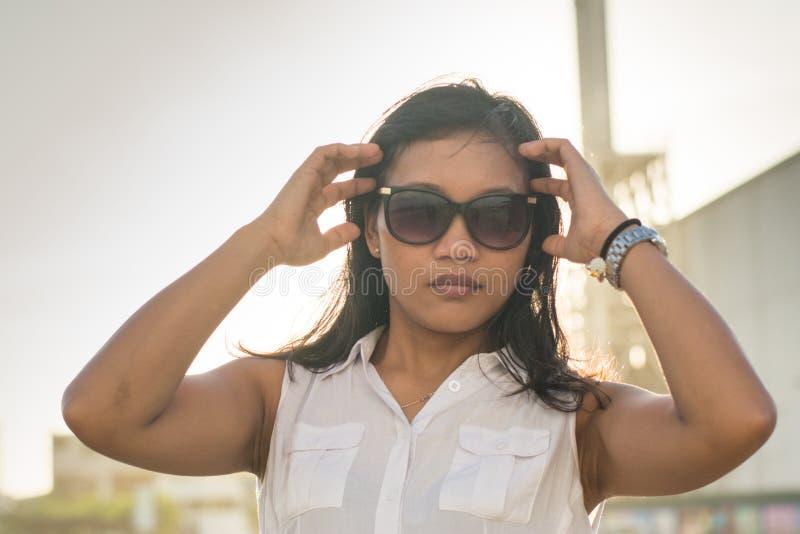 Senhora asiática bonita nos óculos de sol que olham na câmera fotografia de stock
