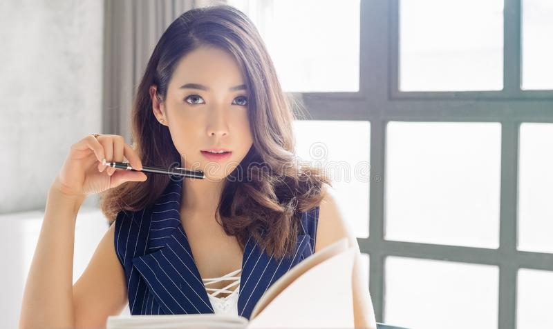A senhora asiática do negócio bonito está olhando a câmera ao trabalhar no escritório fotografia de stock