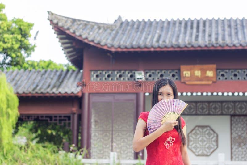 Senhora asiática que veste o cheongsam vermelho no jardim, guardando um fã cor-de-rosa da cor em sua mão imagens de stock royalty free