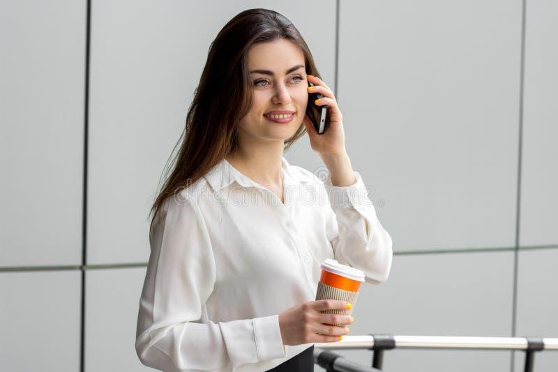 A senhora atrativa do escritório na blusa branca sorri e diz no telefone fotos de stock royalty free