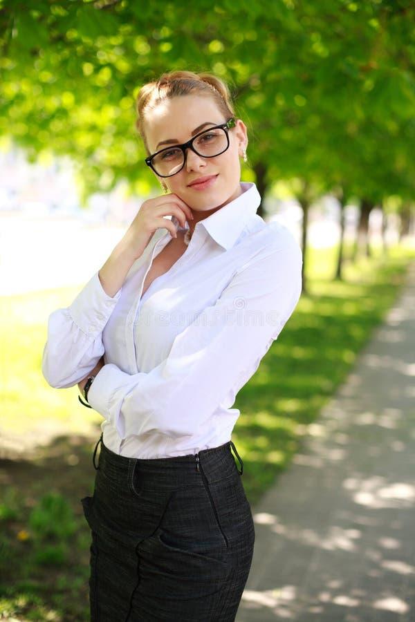 Senhora atrativa do negócio na camisa e nos vidros brancos fotografia de stock
