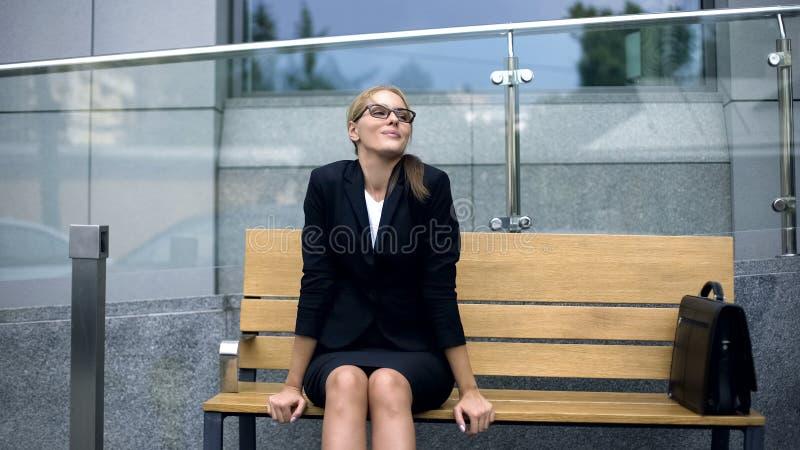 Senhora atrativa do negócio que descansa no banco, admirando a manhã antes do trabalho fatigante imagens de stock