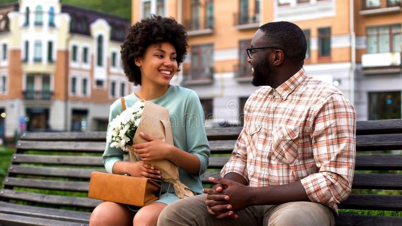 Senhora atrativa que encontra o noivo na primeira data, homem que apresenta as flores brancas imagens de stock