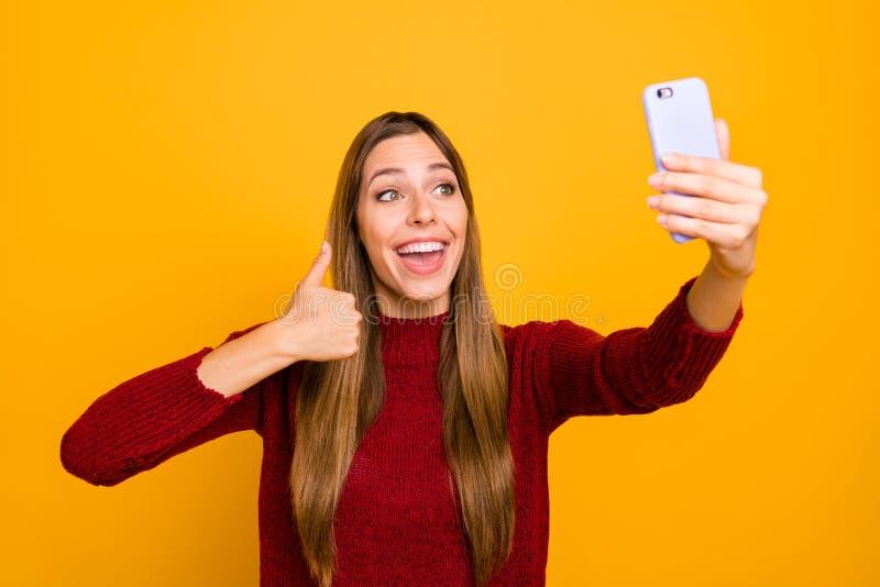 A senhora bonita com as mãos do telefone que fazem o polegar dos selfies aumentado acima do pulôver feito malha desgaste isolou o fotos de stock