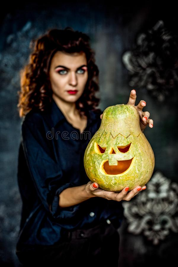 Senhora bonita da bruxa do vampiro que guarda uma lanterna do jaque da cabeça da abóbora de Dia das Bruxas imagens de stock royalty free