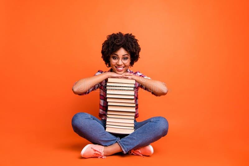 A senhora bonita da foto completa do tamanho de corpo do comprimento senta o assoalho guarda as mãos que os livros retornam para  fotografia de stock