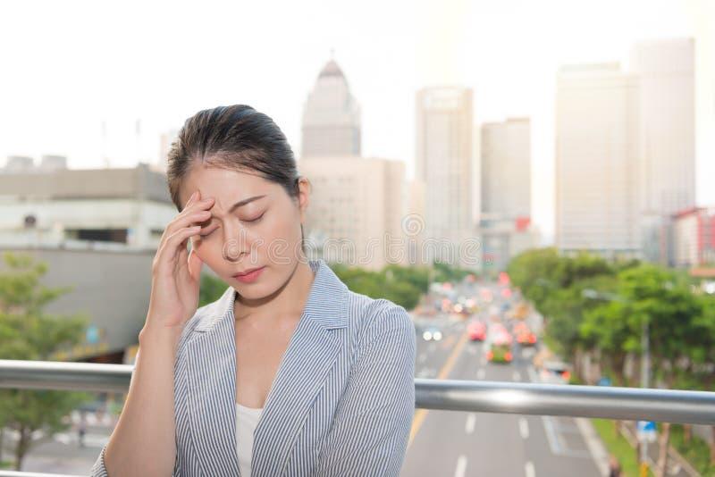 A senhora bonita do escritório sente uma dor de cabeça dolorosa foto de stock royalty free
