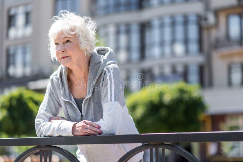 Senhora bonita idosa alegre que tem o resto durante o exercício da manhã fora foto de stock
