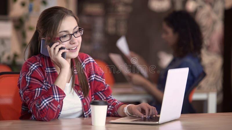 Senhora bonita nos monóculos que trabalham no portátil, telefonema de resposta, autônomo foto de stock royalty free