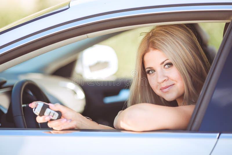Senhora bonita nova com um carro luxuoso moderno imagens de stock royalty free