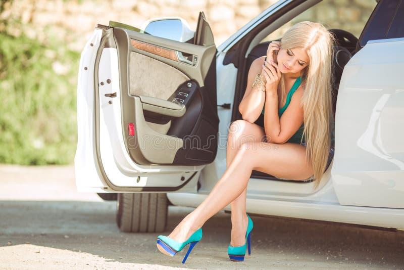 Senhora bonita nova com um carro luxuoso moderno imagem de stock royalty free