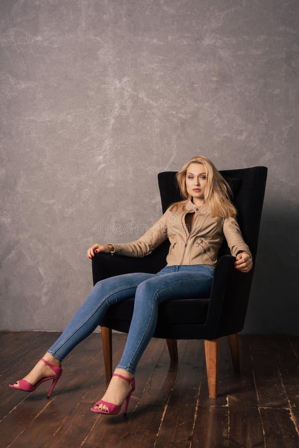 Senhora bonita nova nas calças de brim e um casaco de cabedal que senta-se na poltrona imagem de stock royalty free