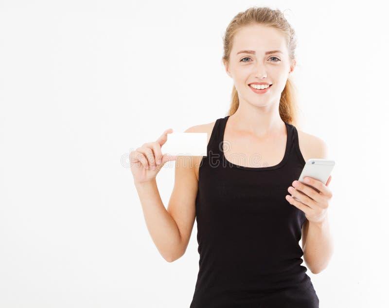 Senhora bonita nova que mantém um telefone e um cartão isolados no branco imagem de stock royalty free