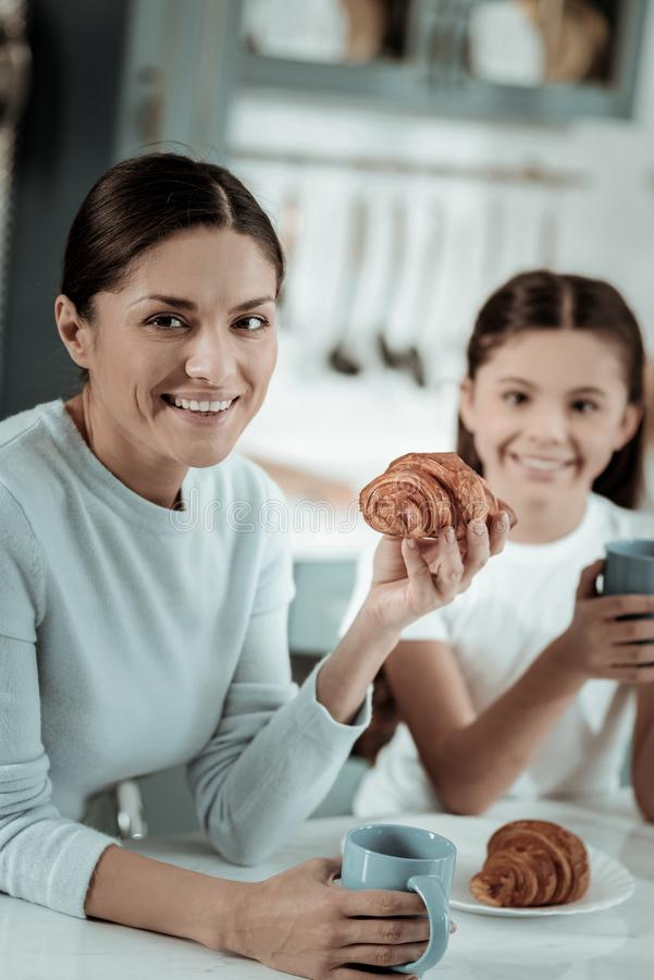 Senhora bonita que come croissant com sua filha fotografia de stock