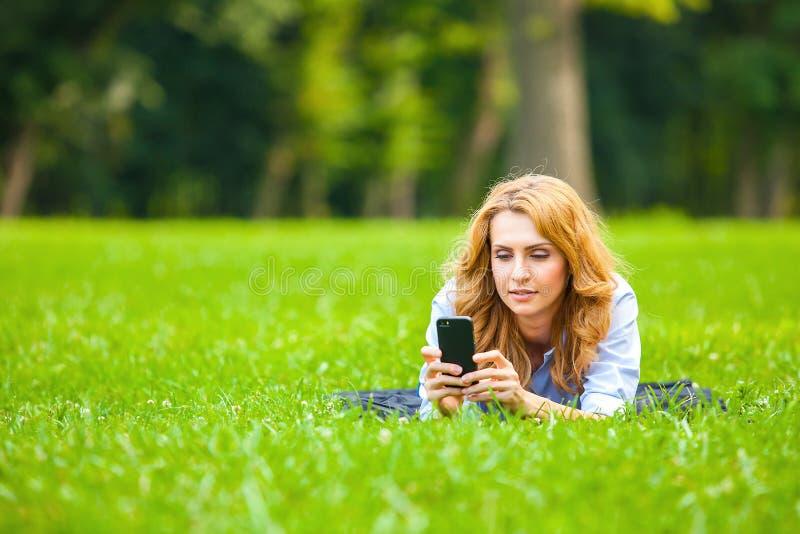 Senhora bonita que fala no telefone celular na grama fotografia de stock royalty free
