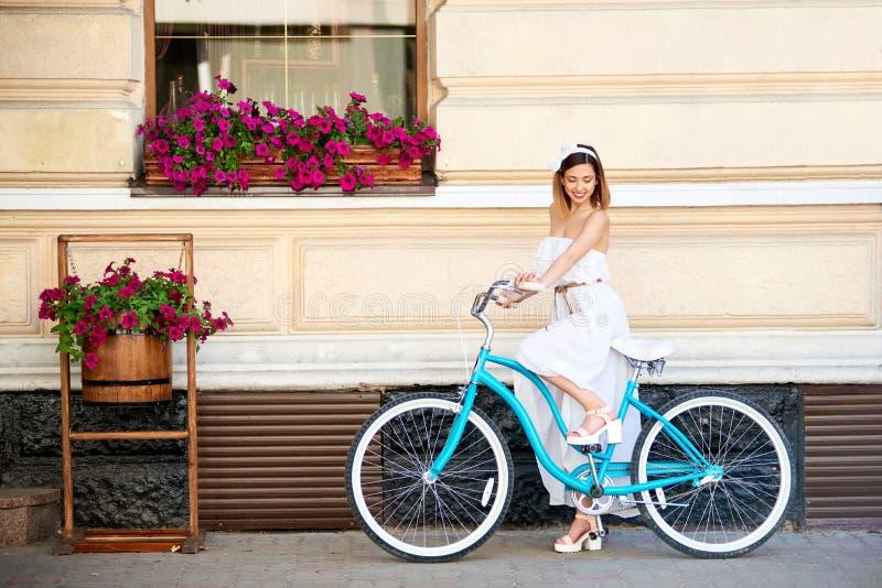 Senhora bonita que monta uma bicicleta azul perto da construção com flores imagens de stock royalty free