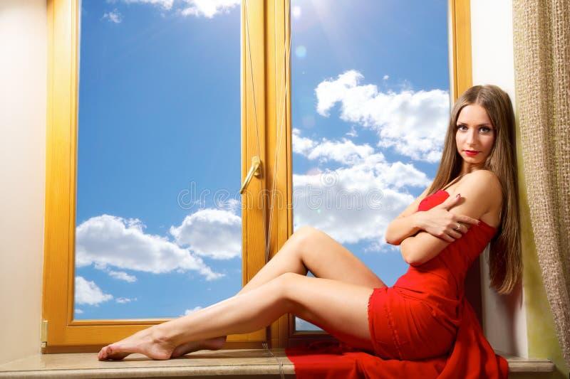Senhora bonita que senta-se na janela fotos de stock