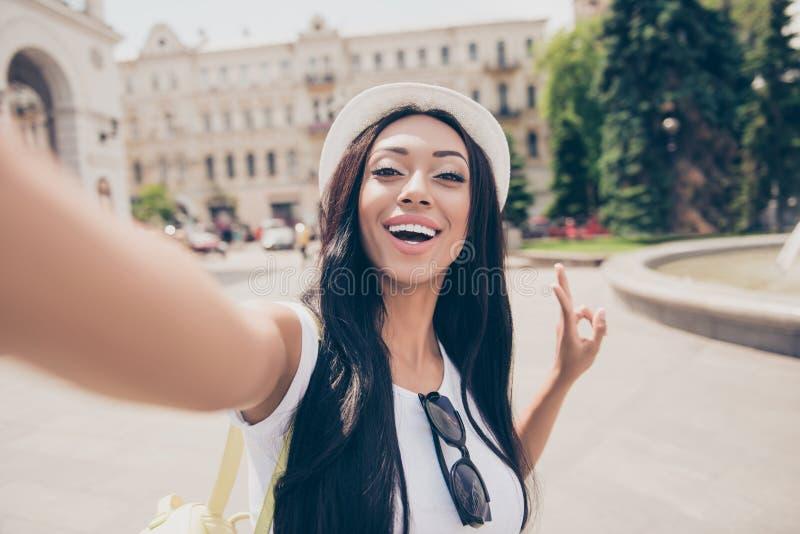 A senhora bonito com pele de bronze e cabelo escuro longo, no tampão está fazendo imagens de stock