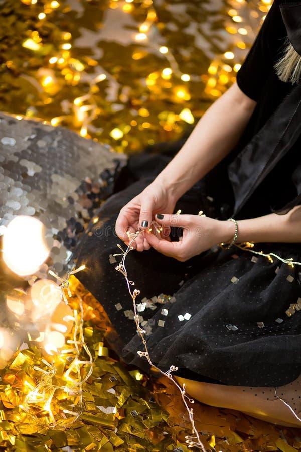 Senhora bonito de surpresa que comemora a festa de anos do ano novo, levantando no fundo do brilho do ouro e jogando confetes col imagens de stock