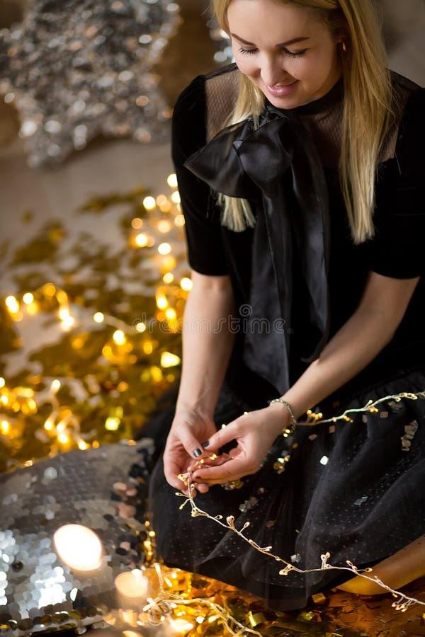 Senhora bonito de surpresa que comemora a festa de anos do ano novo, levantando no fundo do brilho do ouro e jogando confetes col fotos de stock