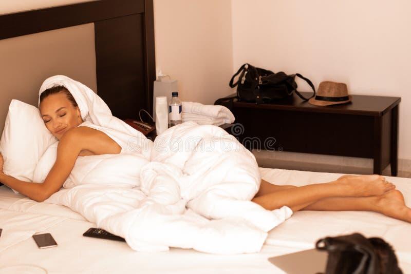 A senhora bonito encontra-se em um hotel branco da cama imagens de stock