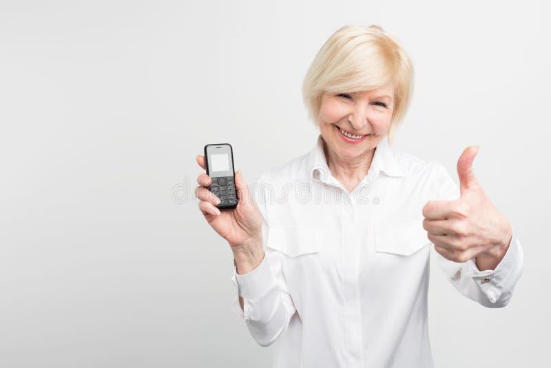 a senhora Branco-de cabelo está guardando um telefone velho Prefere usá-lo em vez de comprar e de usar o novo Este ` t do doesn d imagens de stock royalty free
